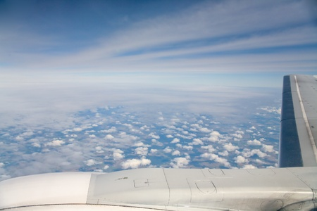 clouds and lands under wing of airplane photo