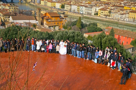 FLORENCE, ITALY - JANUARY 8: Japanese young couple and guests on general picture with view of old Florence during traditional wedding trip in Europe on January 8, 2009 in Florence, Italy.