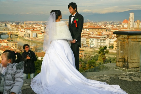 FLORENCE, ITALY - JANUARY 8: Japanese couple takes pictures with view of Florence during traditional wedding trip in Europe on January 8, 2009 in Florence, Italy.