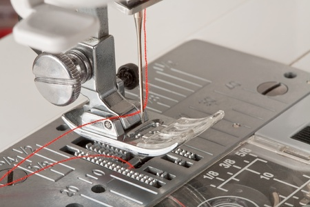 thread in needle of sewing machine closeup photo