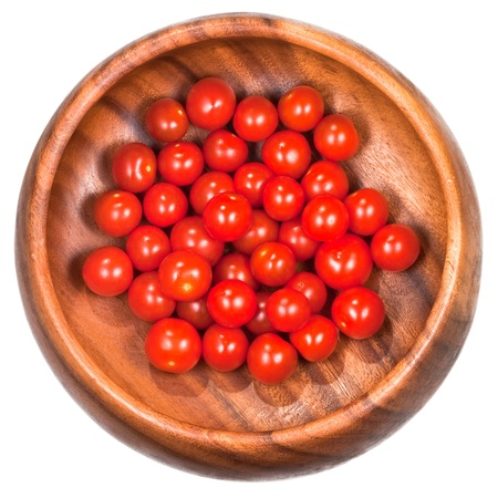 cherry tomatoes: many red cherry tomatoes in wooden bowl