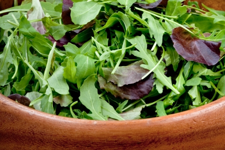 rocket lettuce: fresh salad mix in wooden bowl closeup