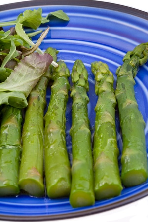 fascicle: boiled green asparagus with salad mix on blue plate