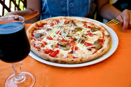 pizza with fungi in Italian outdoor restaurant in summer photo