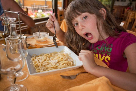 girl eats pasta in italian restaurant in Taormina, Sicily on July, 27, 2011