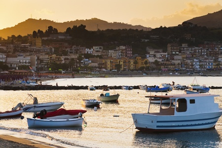 lido: boats at sunset, near town Taormina, Sicily, Italy Stock Photo