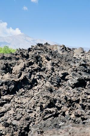 hardened: sharp hardened lava rocks close up with Etna on background Stock Photo