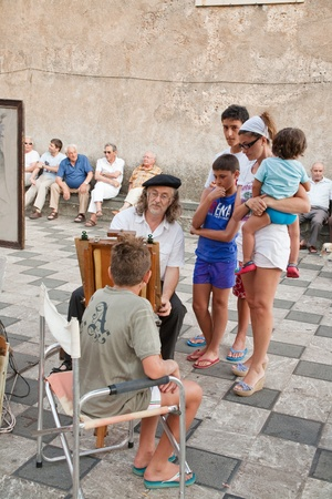 ix portrait: TAORMINA, ITALY - JULY,2: italian street artist and tourists on on Piazza IX Aprile in Taormina, Sicily on July 2, 2011