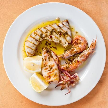 sycylijski: Sycylijczyk grilla mieszanka ryb na białym talerzu Zdjęcie Seryjne