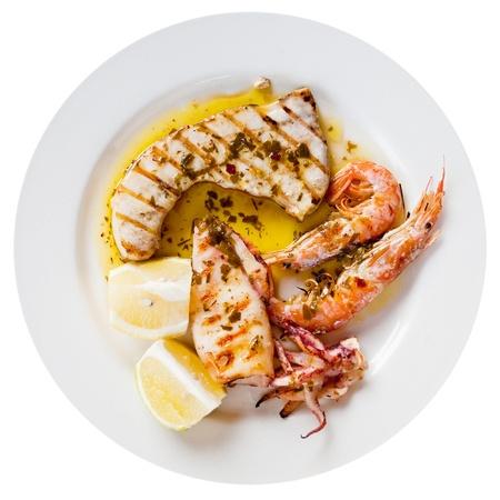 pez espada: mezcla siciliano pescado a la plancha en el plato blanco aislado en blanco