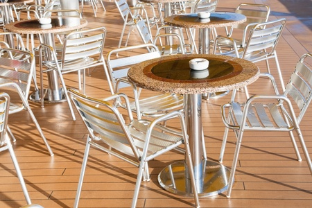 tables with ashtrays in outdoor bar on stern of cruise liner photo