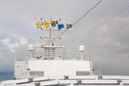 flags of european countries on navigation antenna of cruise liner photo