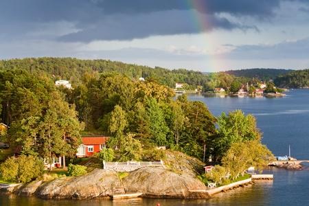 rainbow under small village on Baltic seashore photo