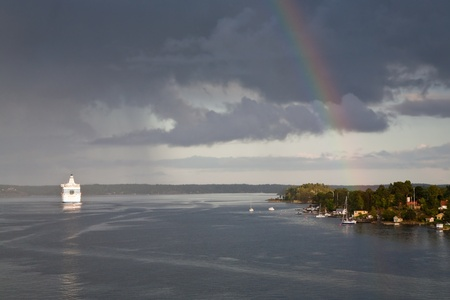 white cruise liner and rainbow in rain during sunshine in Baltic sea photo
