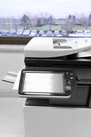 copier: grote grijze copier in grijs kantoor en kleur het leven voorbij venster