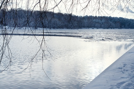 snow-covered beach of river at sunset photo