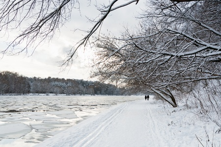 walking path along river with ice floating at evening photo