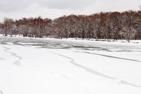 unfrozen patch of water in  icebound river at evening photo