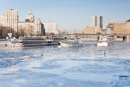 iceboats and fisherman on frozen Moscow river in sunny winter day photo