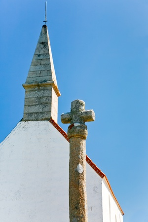 old stone cross and roof of country Chapelle Saint Michel with blue sky background photo