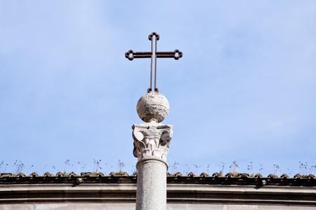 roman catholic: metal medieval cross on blue sky in Rome, Italy
