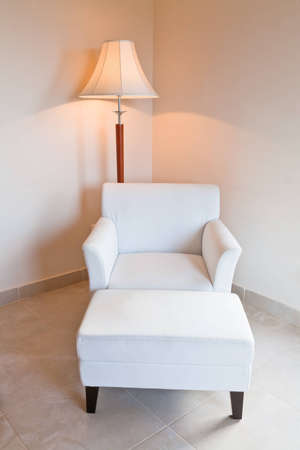 white leather chair and stand lamp in room corner