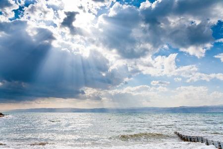 sunbeams though dark blue clouds above Dead Sea photo