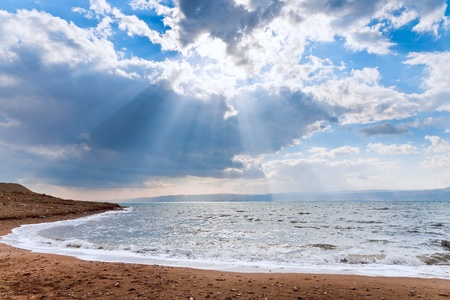 sunbeams though dark blue clouds above Dead Sea Stock Photo