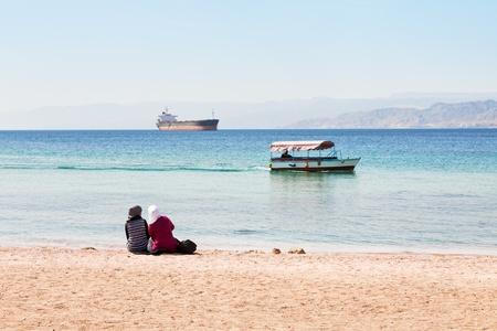 people on urban beach in Aqaba town, view on Aqaba gulf photo