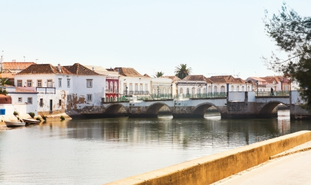 antique bridge through Gilao river in Tavira town, Portugal photo