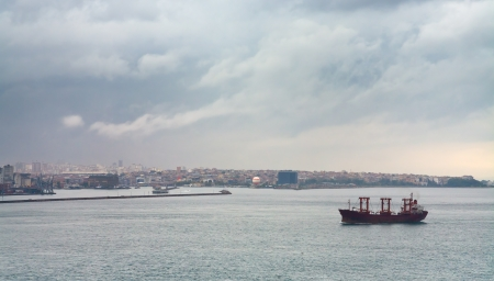 ship in Bosporus gulf and Istanbul view in overcast day photo