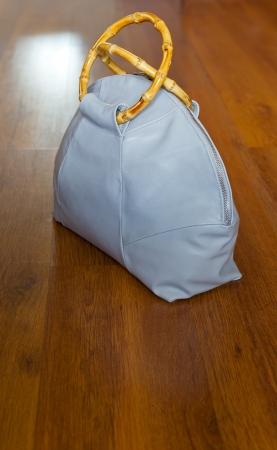 pochette: leather travelling bag on wooden floor