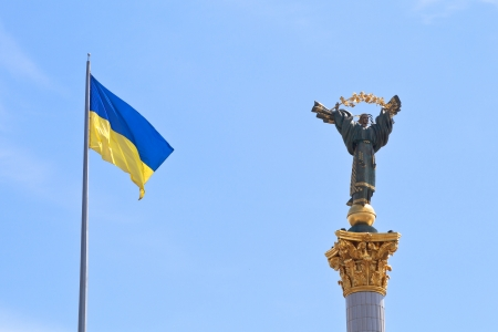 ukrainian flag and Monument to Berehynia in Kiev, Ukraine photo