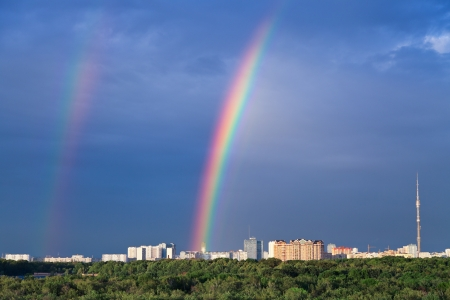 Double rainbow under city park in dark blue sky photo