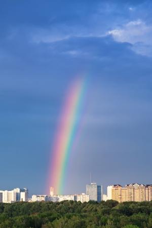 rainbow under city in blue sky photo