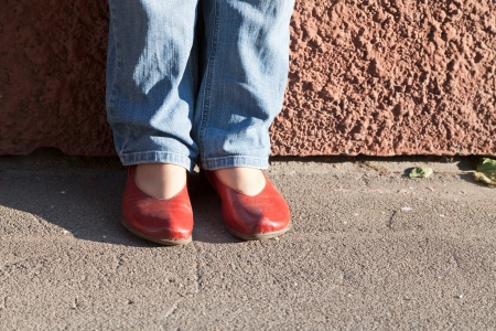 legs in blue jeans and red shoes near wall in autumn day photo
