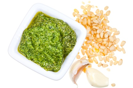 bulbet: top view on italian pesto with fresh pine nuts and garlic cloves isolated on white background Stock Photo