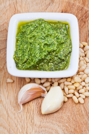 bulbet: italian pesto sauce with pine nuts and garlic cloves on wooden board Stock Photo