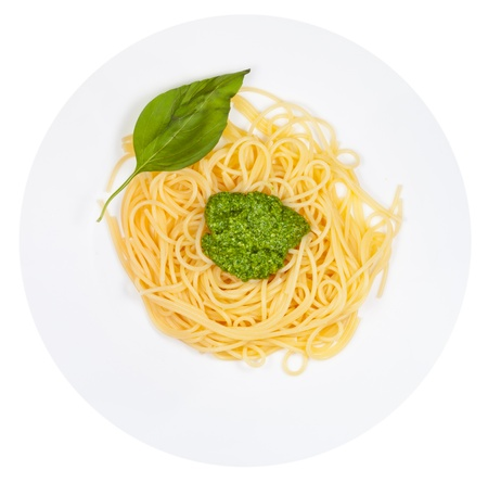 top view on spaghetti with pesto on plate isolated on white background photo