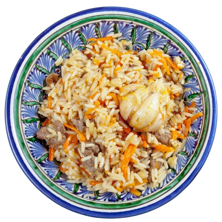 top view on traditional asian pilau with garlic bulb in ceramic bowl isolated on white background photo