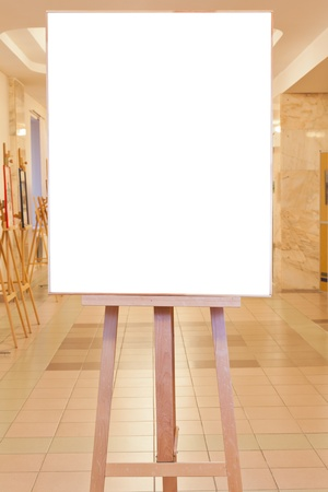big picture frame with white cut out canvas on easel in art gallery photo