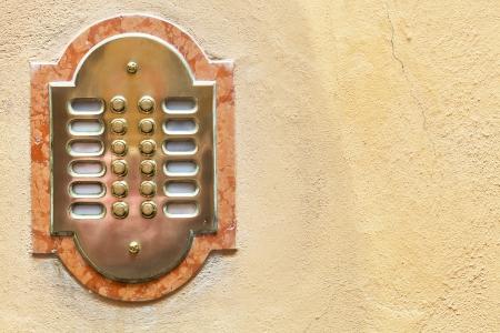 intercommunication: entrance door intercom on yellow house wall