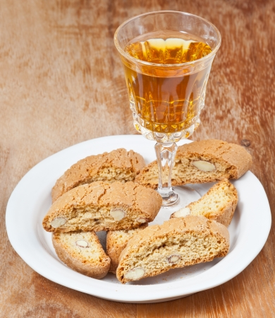 crystal glass with sweet white wine and italian almond cantuccini on saucer on wooden table photo