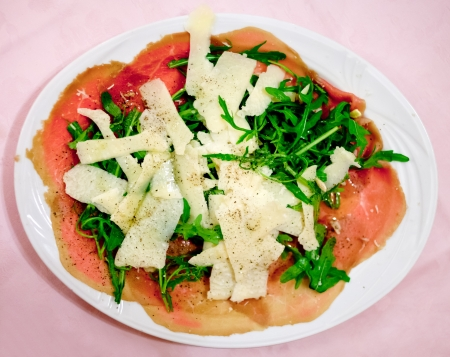 appetize: italian carpaccio with parmesan cheese and arugula on white plate