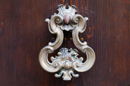 old bronze door handle on dark brown wooden urban door photo