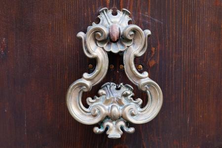 old bronze door handle on dark brown wooden urban door Stock Photo - 16863265