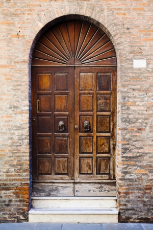 wooden door in brick wall of medieval house in Ferrara, Italy photo