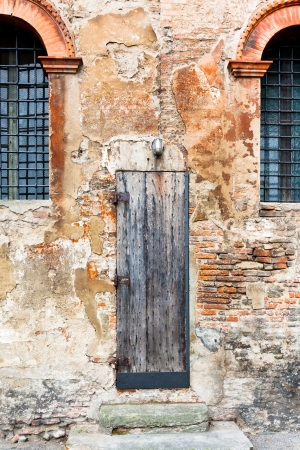 old wooden door in shabby brick wall of medieval house in Bologna, Italy