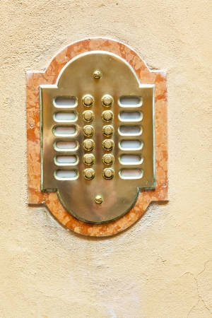 entrance door intercom on yellow house wall photo