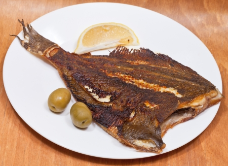 fried sole fish on white plate on wooden table photo